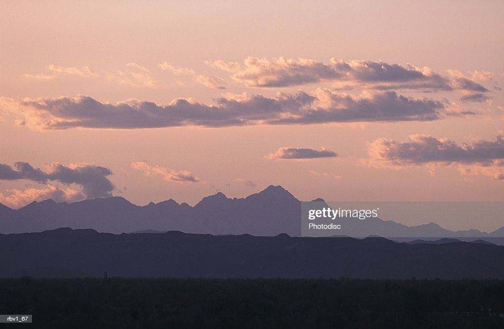 white clouds rise above dark mountains as the sun sets leaving a pink sky : Foto de stock