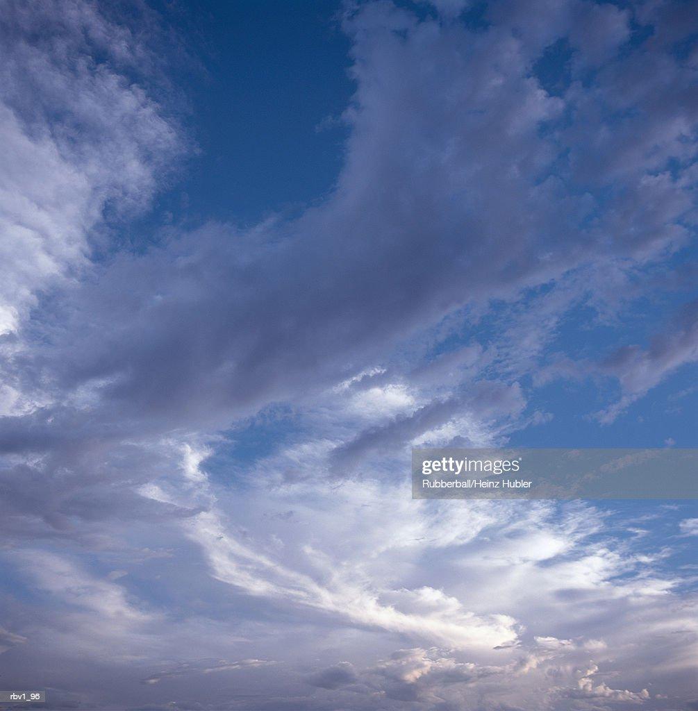 white clouds swirl in a blue sky : Foto de stock
