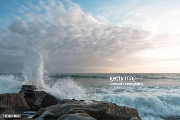 white clouds with waves crashing on a rock formation at moffat beach, queensland - fels stock-fotos und bilder