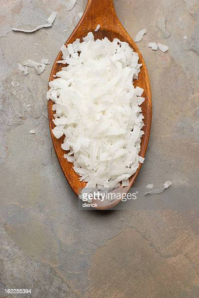 White coconut flakes in a wooden spoon on a table