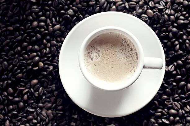 White coffee cup in middle of coffee beans