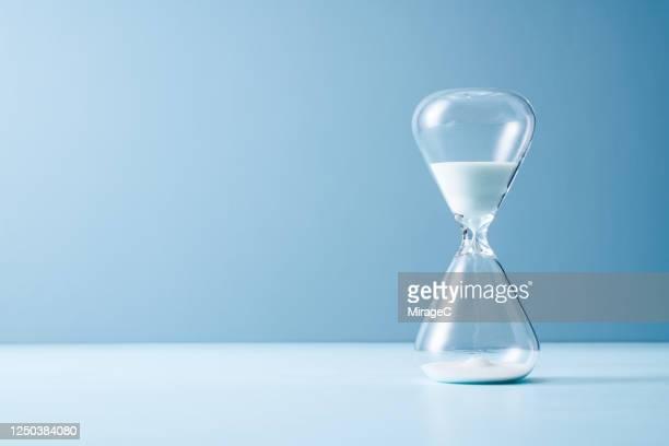 white colored sand hourglass - ampulheta imagens e fotografias de stock