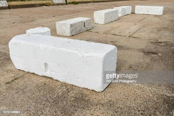 white concrete road blocks on a concrete road - construction barrier stock pictures, royalty-free photos & images