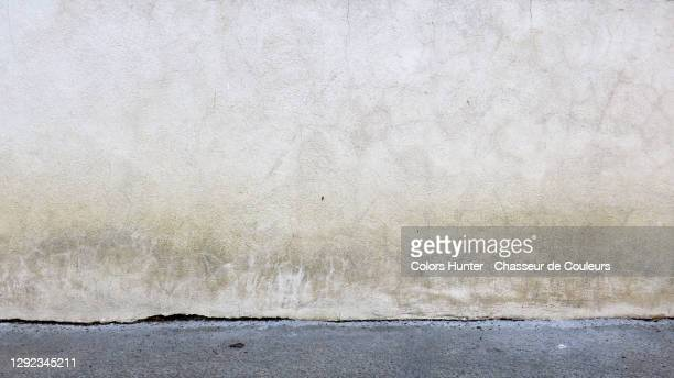 white concrete wall with patina and gray sidewalk in paris - wall building feature stock pictures, royalty-free photos & images