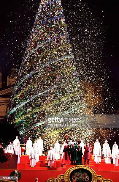 White confetti falls like snow over Japan's largest 36metertall Christmas tree while a chorus sings carols at Universal Studios Japan in Osaka...