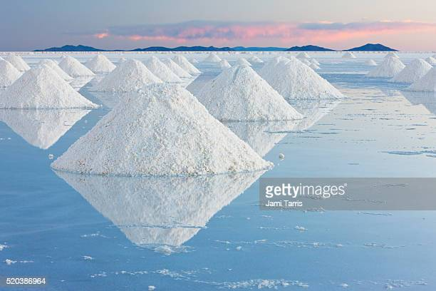 white conical mounds of salt reflect the clear water on salar de uyuni in the pink light of sunset - bolivia stock pictures, royalty-free photos & images