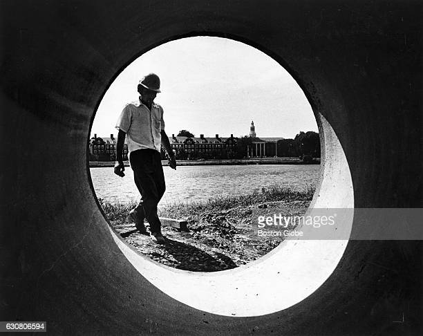 F White Construction Company employee Vasco Resendes of New Bedford Mass prepares to fasten a nut and bolt on a concrete pipe to be lifted into place...