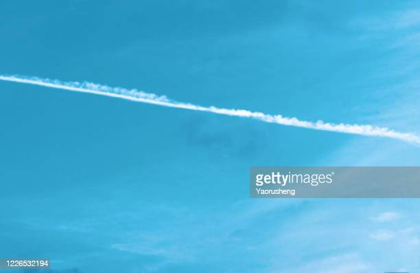white contrails of planes on the background of the blue sky. - chemtrails stock-fotos und bilder