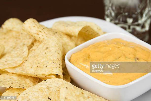 white corn tortilla chips and cheese dip - cheese sauce stock photos and pictures