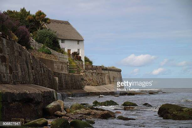 White cottage with thatched roof overlooking bay. Blue skies and sunshine. Rocks in foreground.