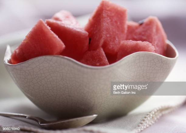 A white crackle-glazed bowl with watermelon pieces with a white cloth napkin and a spoon
