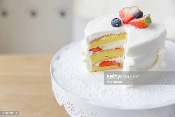 A white cream fruit cake on a cake stand is put on a wooden table