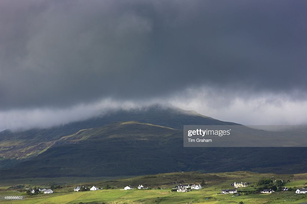 White croft cottages nestled under a mountain and grey clouds near Harlosh on the Isle of Skye, Western Isles of Scotland, UK