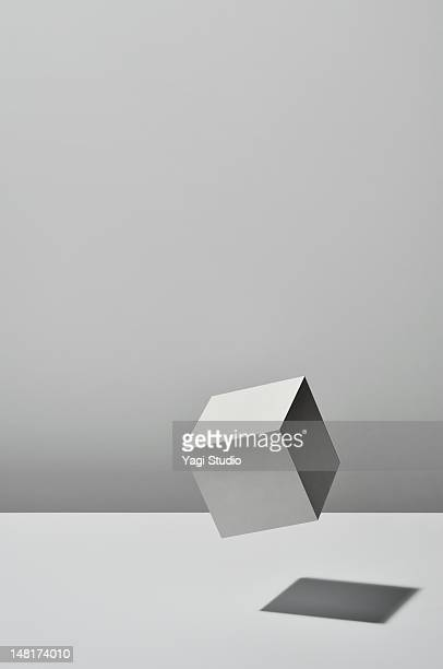 white cube is floating on white background - 立方体 ストックフォトと画像