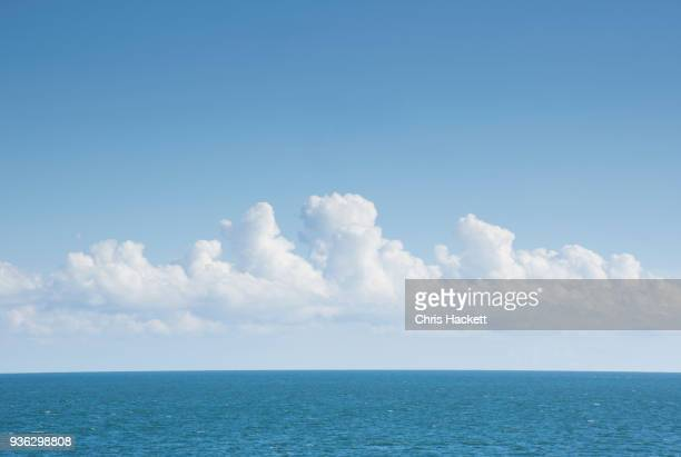 white cumulus clouds above blue atlantic ocean - nuvens fofas imagens e fotografias de stock