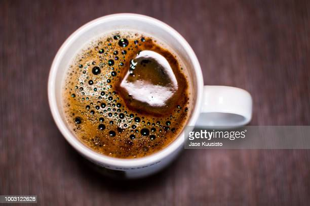 white cup of black coffee on a brown textured coffee table - caffeine stock pictures, royalty-free photos & images
