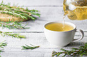 White cup of healthy rosemary tea pouring from teapot with fresh rosemary bunch on white wooden rustic background, winter herbal hot drink concept, salvia rosmarinus