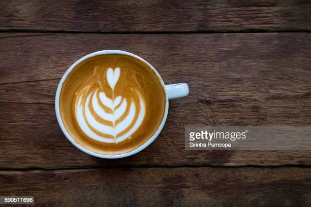 a white cup of hot latte art coffee on the wooden table in coffee shop - wood table top stock photos and pictures