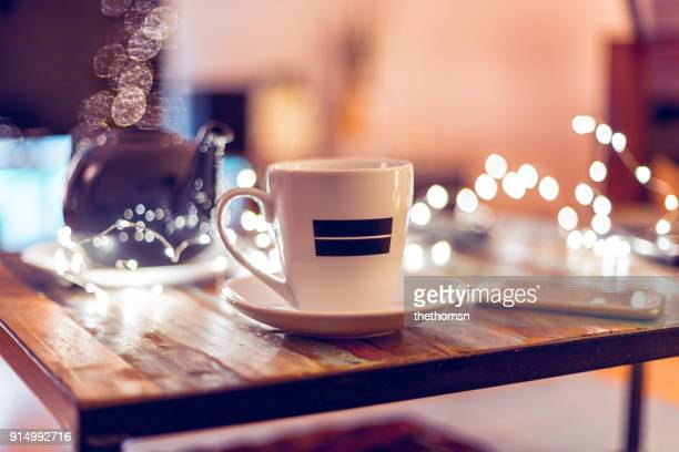 White cup with black stripes on coffee table against defocused lights