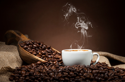 White cup with coffee beans on dark background 489377142