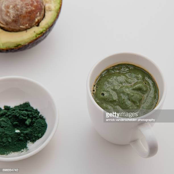 White cup with delicious raw soup with avocado and spirulina.