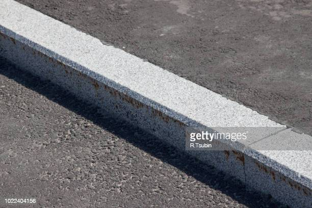 white curb stone border and asphalt road - curb stock pictures, royalty-free photos & images
