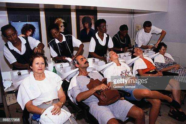 White customers have their hair washed by black workers at Carlton Hair International a hair salon in the exclusive Hyde Park shopping center in...