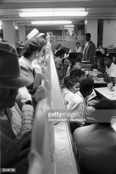 White customers look over a railing at black protesters gathered at a desegregation 'sitin' at Brown's Basement Luncheonette in Oklahoma