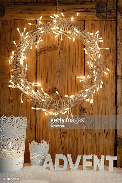 White decoration with lighted Advent wreath in front of wooden wall