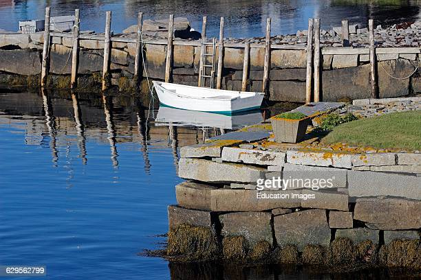 White dingy and granite wharfs in harbor Vinalhaven Island Maine New England USA