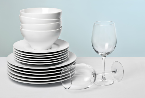 White dishes and crystal wine glasses on varied blue background 147276139