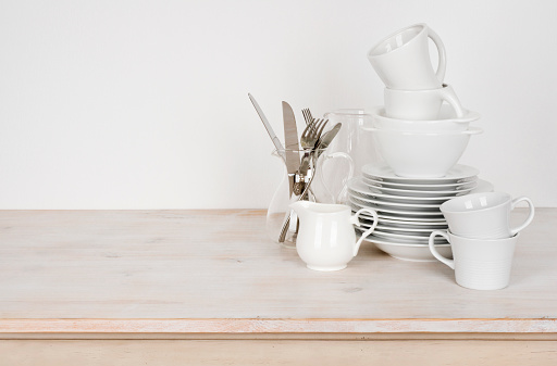 White dishware and cutlery on wooden table with copy space 629746408