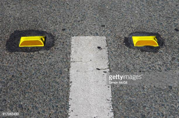 White dividing line and yellow plastic road reflectors on a city street