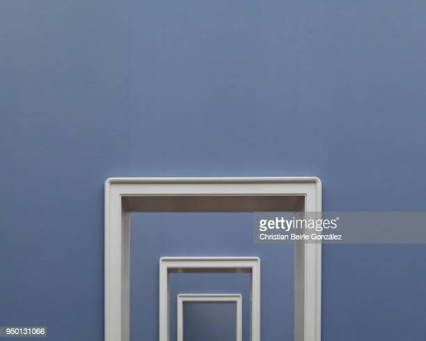 white doorframes on blue wall - christian beirle stockfoto's en -beelden