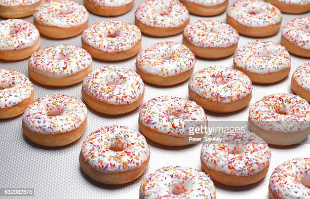 white doughnuts on production line - food and drink industry stock pictures, royalty-free photos & images