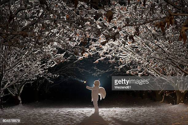 white dressed child with angel wings holding a light in cold winter's night - snow angel fotografías e imágenes de stock