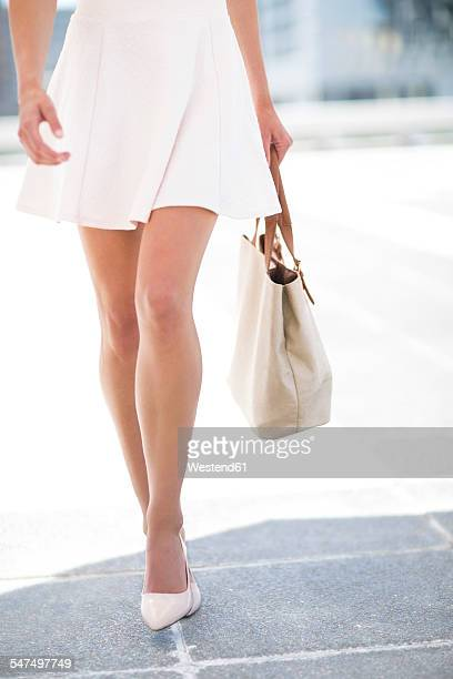white dressed woman with handbag - white skirt stock photos and pictures