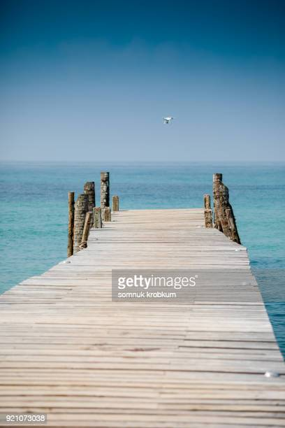 White drone flying over wooden walk path with blue sea in summer