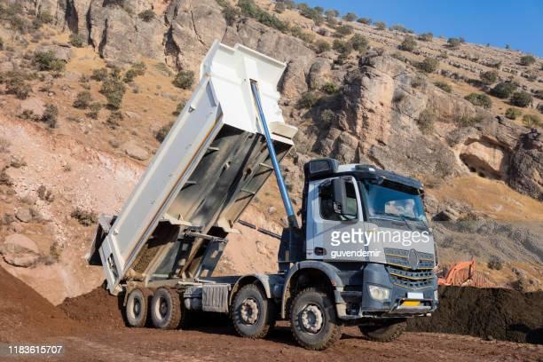 土壌を降ろす白いダンプトラック - ダンプカー ストックフォトと画像