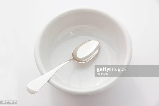 White empty bowl with silver spoon on white