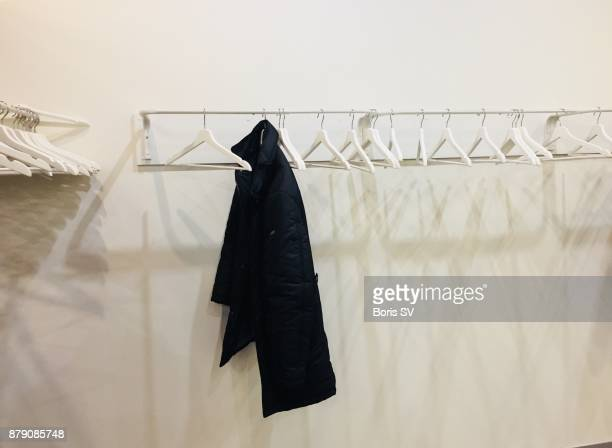 White empty hangers with one black coat