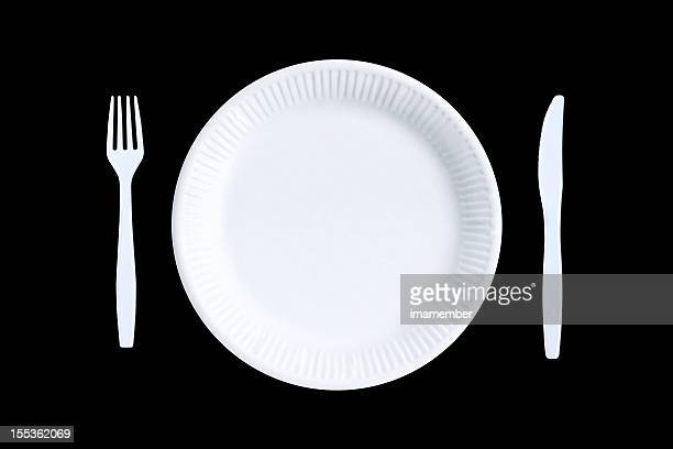 White empty paper plate and white plastic cutlery, black background