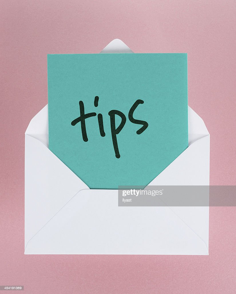White envelope containing blue tips on pink background : Stock Photo