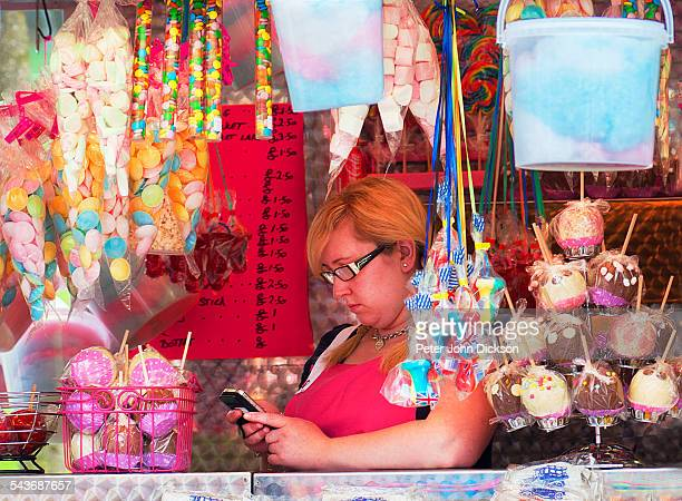 A white European female using a cellphone on a candy/sweet store at Goose Fair Nottingham UK