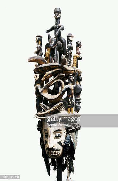 White faced Igbo mask with two tiered superstructure of polychromed figures including a horse and rider and pythons Nigeria Igbo 20th c...