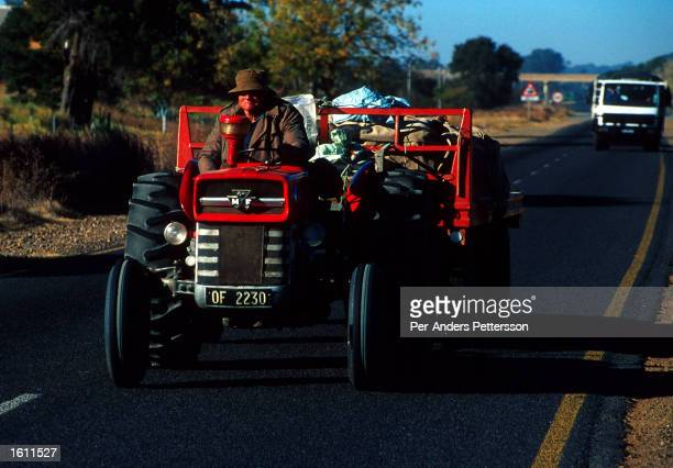A white farmer transports goods on his tractor June 22 2001 outside Vryburg a farming town about 400 kilometers west of Johannesburg South Africa The...