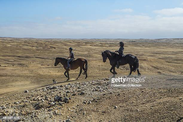 A White Female And A Black Male Couple Riding Their Horse On A Trail At Swakopmund In Nmibia
