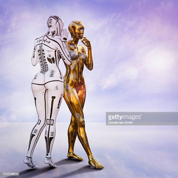 White female cyborg standing and whispering to gold cyborg