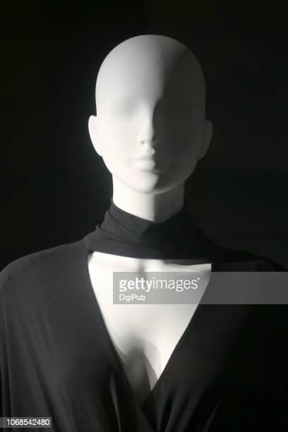 white female like mannequin wearing black dress on black background - マネキン人形 ストックフォトと画像