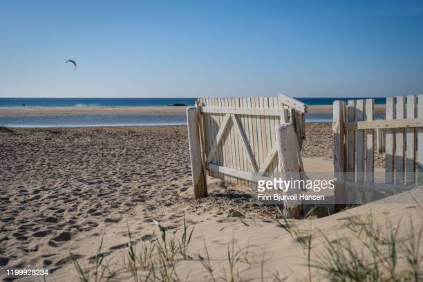 white fence on the beach of tarifa spain - finn bjurvoll stock pictures, royalty-free photos & images